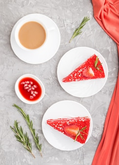 Zelfgemaakte rood fluwelen cake met melk crème en aardbei met kopje koffie op een grijze betonnen achtergrond. bovenaanzicht, close-up.