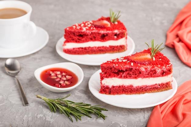 Zelfgemaakte rood fluwelen cake met melkroom en aardbei met kopje koffie op een grijs beton.