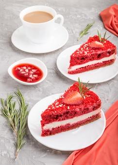 Zelfgemaakte rood fluwelen cake met melkroom en aardbei met kopje koffie op een grijze betonnen ondergrond met rode textiel