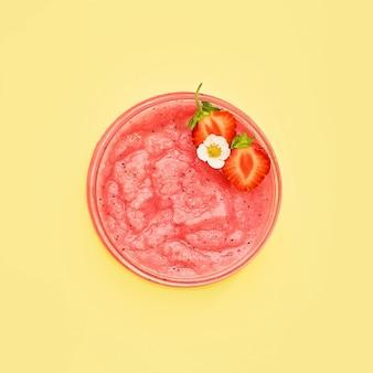 Zelfgemaakte roze bodyscrub met aardbei in een glazen pot op een gele achtergrond. spa-concept. selectieve focus