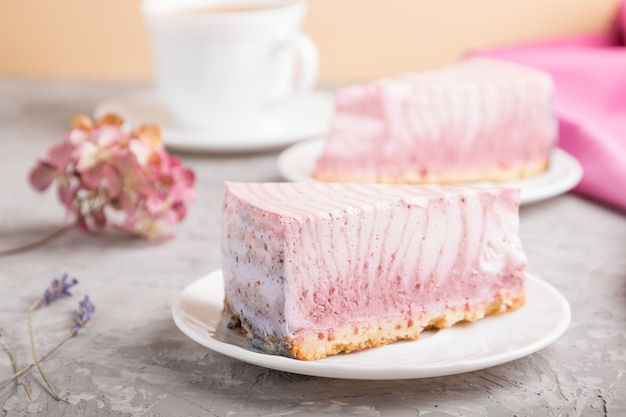 Zelfgemaakte roze cheesecake met kopje koffie. zijaanzicht