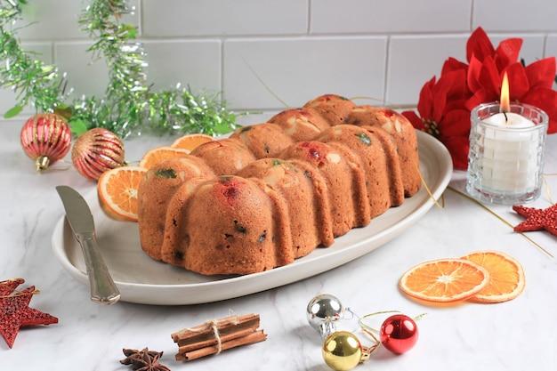Zelfgemaakte rum christmas gedroogd fruit cake pudding voor familiefeest. geserveerd op bruine cementtafel met gedroogde sunkist