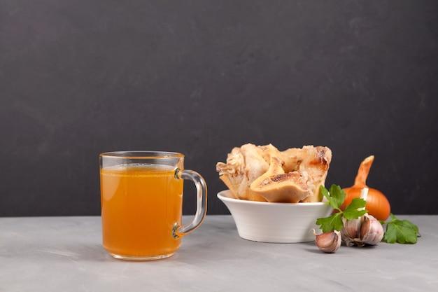 Zelfgemaakte runderbouillon met natuurlijk collageen, vloeibare bouillon in transparante mok. kom met gekookte botten.