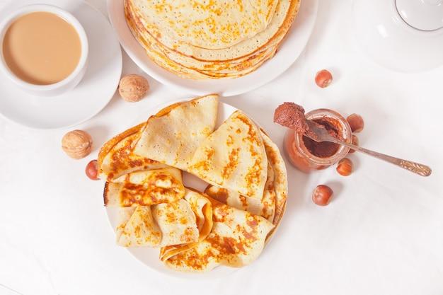 Zelfgemaakte russische dunne smakelijke pannenkoeken op de plaat met chocolade roomsaus.