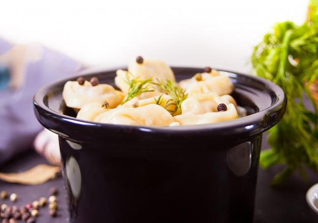 Zelfgemaakte russische pelmeni vlees dumplings italiaanse ravioli in de kleine zwarte pan.