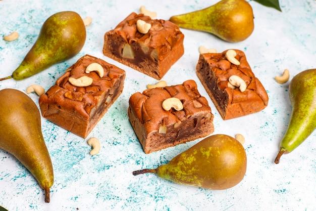 Zelfgemaakte rustieke chocolade cake met peer en cashewnoten, bovenaanzicht