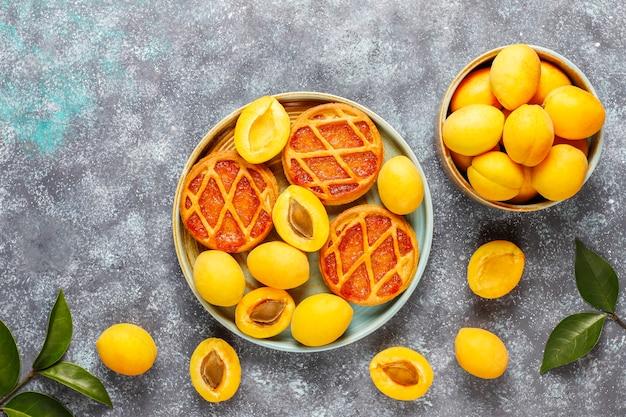 Zelfgemaakte rustieke mini abrikozentaarten met verse abrikozenvruchten