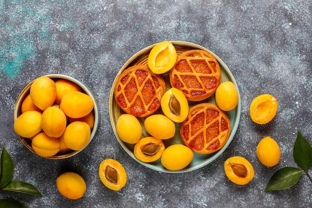 Zelfgemaakte rustieke mini-abrikozentaartjes met verse abrikozenvruchten