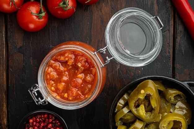 Zelfgemaakte salsa sauzen, op oude donkere houten tafel tafel, bovenaanzicht plat lag