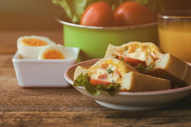 Zelfgemaakte sandwich met hardgekookte eieren en mayonaise gedecoreerd met sla en tomaat