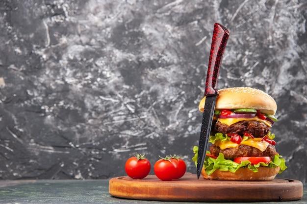 Zelfgemaakte sandwich tomaten ketchup mes op houten snijplank op donkere kleur oppervlak met vrije ruimte