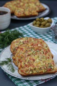 Zelfgemaakte sandwiches met kaas en worst voor het bakken op perkament op een bakplaat, het kookproces, verticale oriëntatie