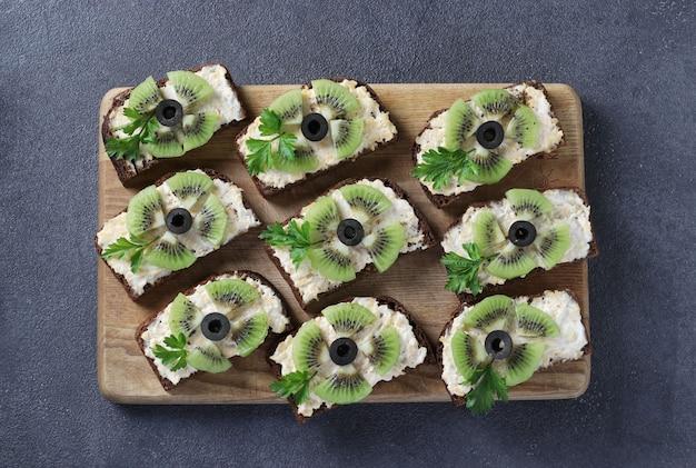 Zelfgemaakte sandwiches met kiwi, kaas, knoflook en zwarte olijven op houten bord op grijze achtergrond