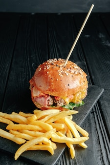 Zelfgemaakte sappige hamburger op donkere houten bord.