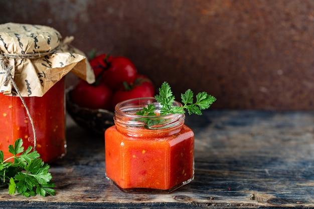 Zelfgemaakte saus gemaakt van rijpe rode tomaten in glazen potten