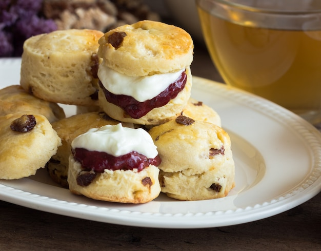 Zelfgemaakte scones van rozijnen serveren zelfgemaakte aardbeienjam, clotted cream en thee.