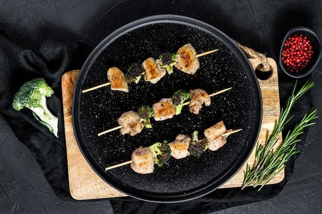 Zelfgemaakte shish kebab van kippendij vlees. zwarte achtergrond. bovenaanzicht