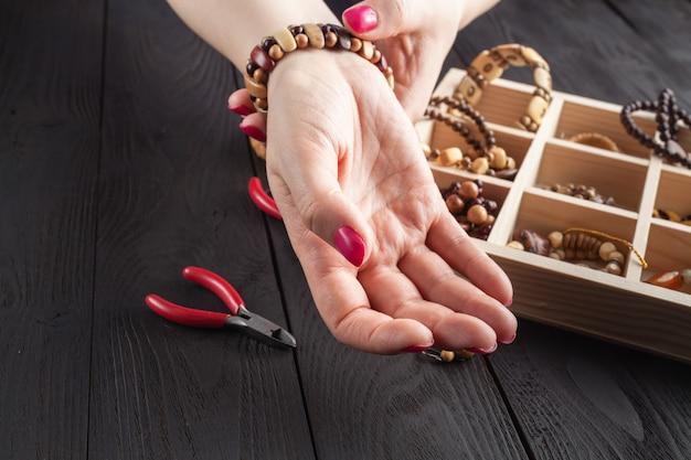Zelfgemaakte sieraden. vrouw die de kunstbijouterie van de huisambacht maken