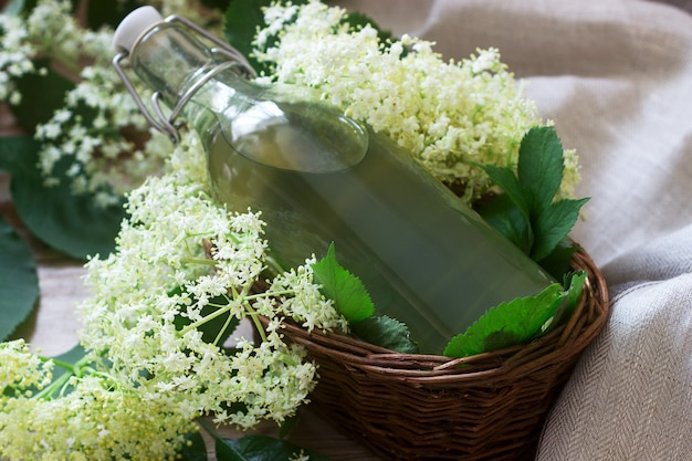 Zelfgemaakte siroop van vlierbessen bloemen in een glazen pot en vlier takken op een houten tafel rustieke stijl.