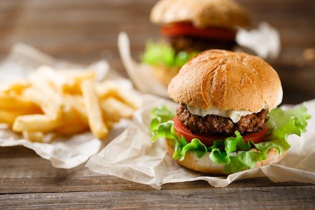 Zelfgemaakte smakelijke hamburger en frietjes op houten tafel