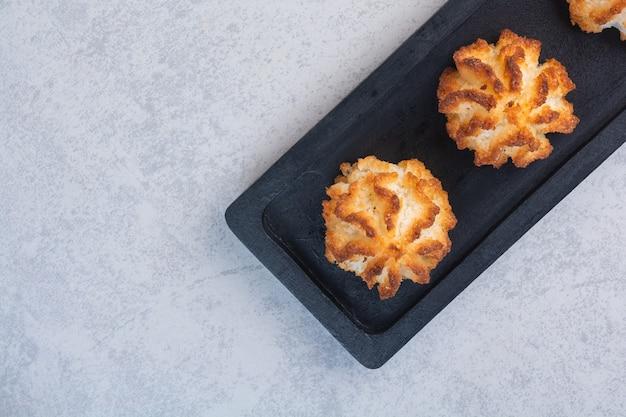 Zelfgemaakte smakelijke koekjes op een bord, op de marmeren achtergrond.
