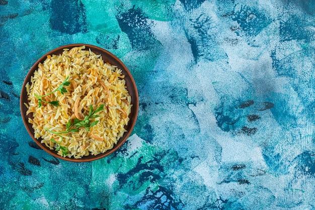 Zelfgemaakte smakelijke noedels in een kom, op de blauwe achtergrond.