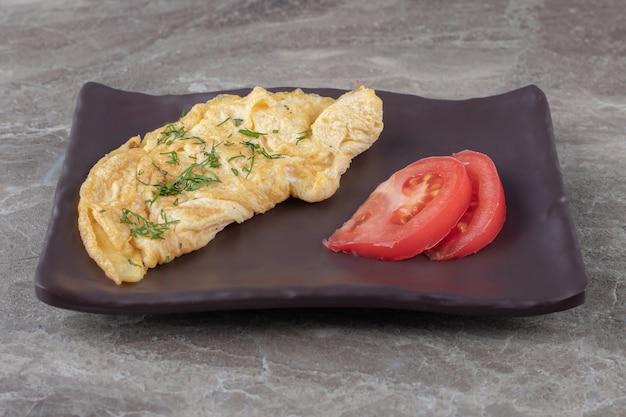 Zelfgemaakte smakelijke omelet met tomaat op donkere plaat.