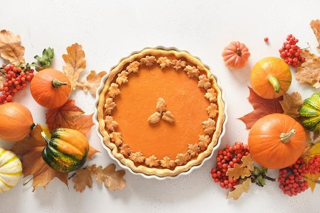 Zelfgemaakte smakelijke pompoentaart met herfstdecoraties en bladeren voor thanksgiving day op wit