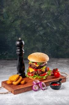 Zelfgemaakte smakelijke sandwich en tomaten kipnuggets uien peper op houten snijplank ketchup op wazig oppervlak in verticale weergave