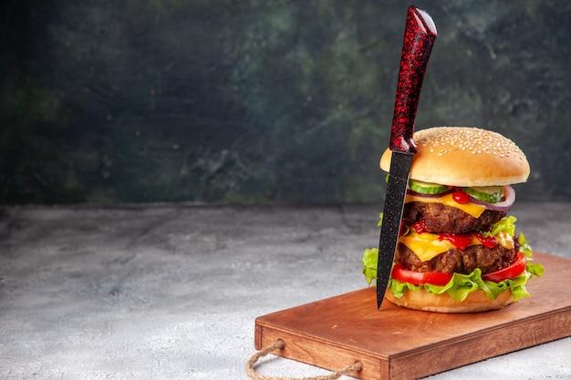 Zelfgemaakte smakelijke sandwich en vork op houten snijplank aan de linkerkant op wazig oppervlak