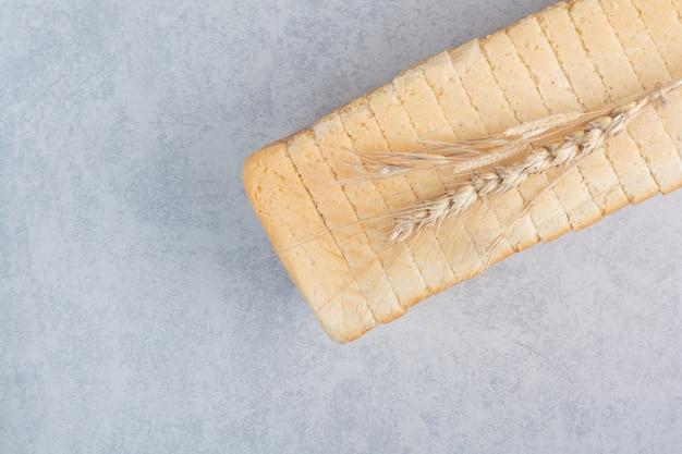 Zelfgemaakte sneetjes brood op stenen oppervlak met tarwe