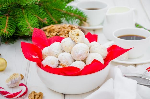 Zelfgemaakte sneeuwballen cookies met walnoten in poedersuiker in een kom