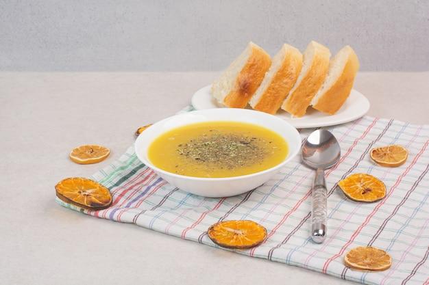 Zelfgemaakte soep en sneetjes brood op tafellaken.