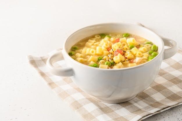 Zelfgemaakte soep met ditalinideegwaren, erwten, ham op witte lijst. detailopname. kopieer ruimte.