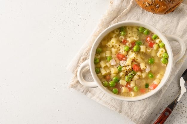 Zelfgemaakte soep met ditalinideegwaren, erwten, ham op witte lijst.