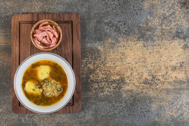 Zelfgemaakte soep met gehaktballen op een houten bord.