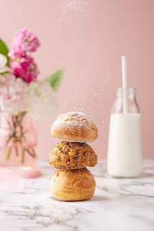 Zelfgemaakte soesjes met vla bedekt suikerpoeder op marmeren tafel op roze achtergrond met bloemen en melk verticaal