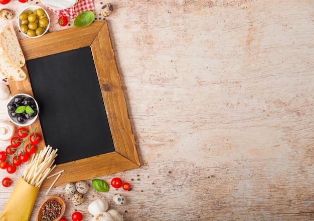 Zelfgemaakte spaghetti pasta met kwarteleitjes en houtskool menu bord en kaas. klassiek italiaans dorpsvoedsel. knoflook, champignons, zwarte en groene olijven, houten spatel.