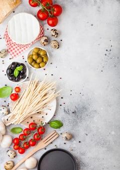 Zelfgemaakte spaghetti pasta met kwarteleitjes met fles tomatensaus en kaas. klassiek italiaans dorpsvoedsel. knoflook, champignons, zwarte en groene olijven, pan en spatel