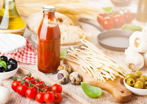 Zelfgemaakte spaghetti pasta met kwarteleitjes met fles tomatensaus en kaas. klassiek italiaans dorpsvoedsel. knoflook, zwarte en groene olijven, olie en brood.
