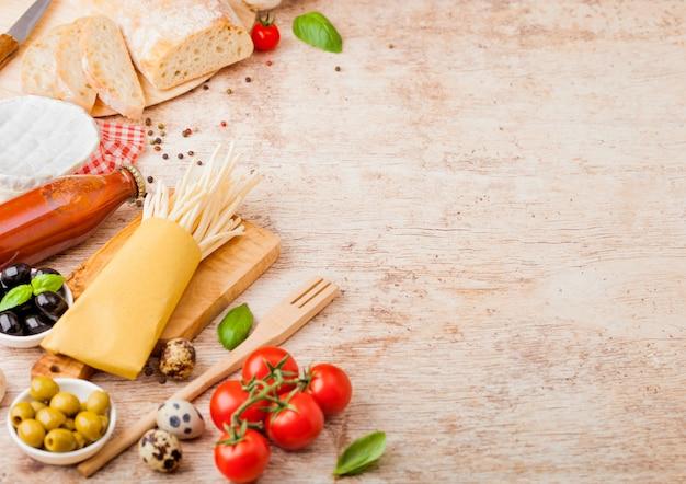 Zelfgemaakte spaghetti pasta met kwarteleitjes met fles tomatensaus en kaas op houten tafel. klassiek italiaans dorpsvoedsel. knoflook, champignons, zwarte en groene olijven, brood en spatel.