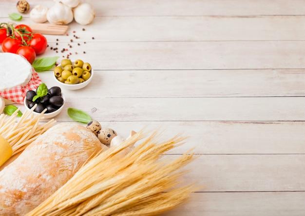 Zelfgemaakte spaghetti pasta met kwarteleitjes met fles tomatensaus en kaas op houten tafel. klassiek italiaans dorpsvoedsel. knoflook, champignons, zwarte en groene olijven, brood en tarwe
