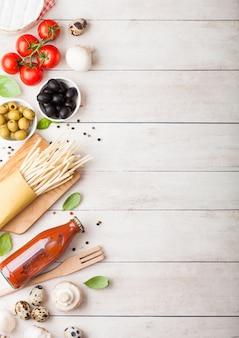 Zelfgemaakte spaghetti pasta met kwarteleitjes met fles tomatensaus en kaas op houten tafel. klassiek italiaans dorpsvoedsel. knoflook, champignons, zwarte en groene olijven, olie en spatel