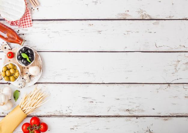 Zelfgemaakte spaghetti pasta met kwarteleitjes met fles tomatensaus en kaas op houten tafel. klassiek italiaans dorpsvoedsel. knoflook, champignons, zwarte en groene olijven