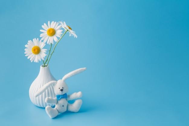 Zelfgemaakte speelgoed konijn met een boeket van madeliefjebloemen