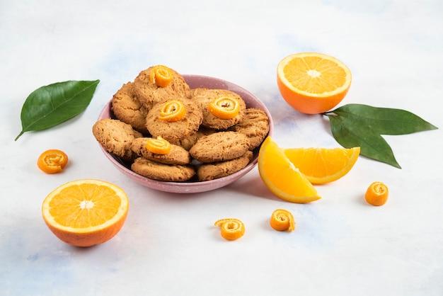 Zelfgemaakte stapel koekjes in roze kom en sinaasappel gesneden of half gesneden over wit oppervlak.