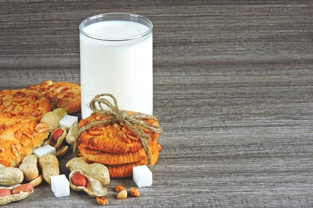 Zelfgemaakte suikerkoekjes met pinda's en een glas verse melk.
