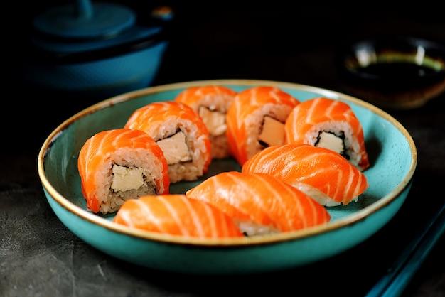 Zelfgemaakte sushi rolt philadelphia en nigiri in een blauw bord op een zwarte ondergrond.