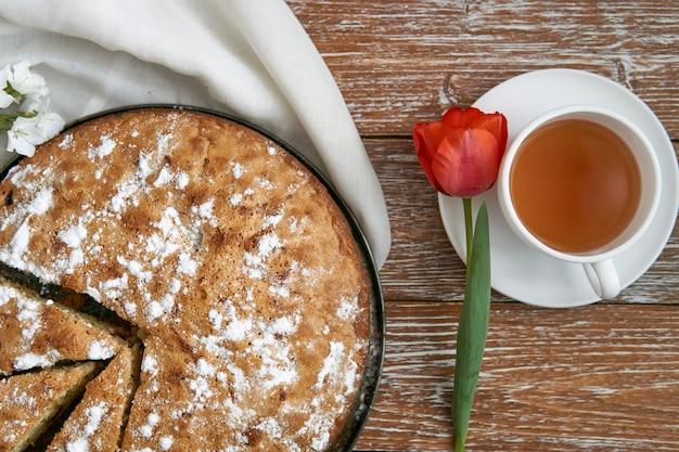 Zelfgemaakte taart met kersen en appels witte kopje thee. eten in rustieke stijl