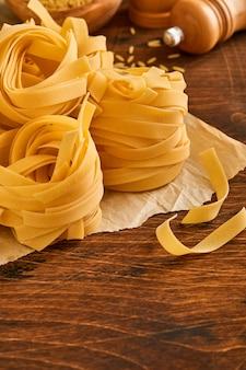 Zelfgemaakte tagliatelle pasta in bruin papier op een oude houten ondergrond